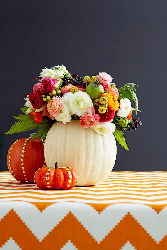 ein tisch mit einer orangen decke, eine vase aus einem großen weißen kürbis und mit vielen violetten, gelben und roten blumen und rosen mit grünen blättern, zwei orange kürbisse, halloween deko selbst basteln
