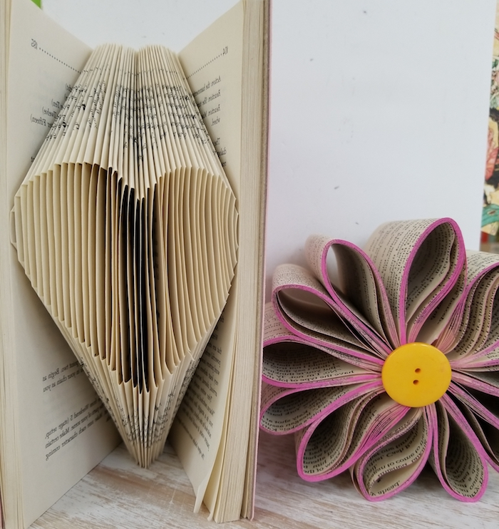 eine violette blume aus papier und ein herz aus vielen gelben alten und gefalteten seiten mit kleinen schwarzen buchstaben, bücher falten ideen