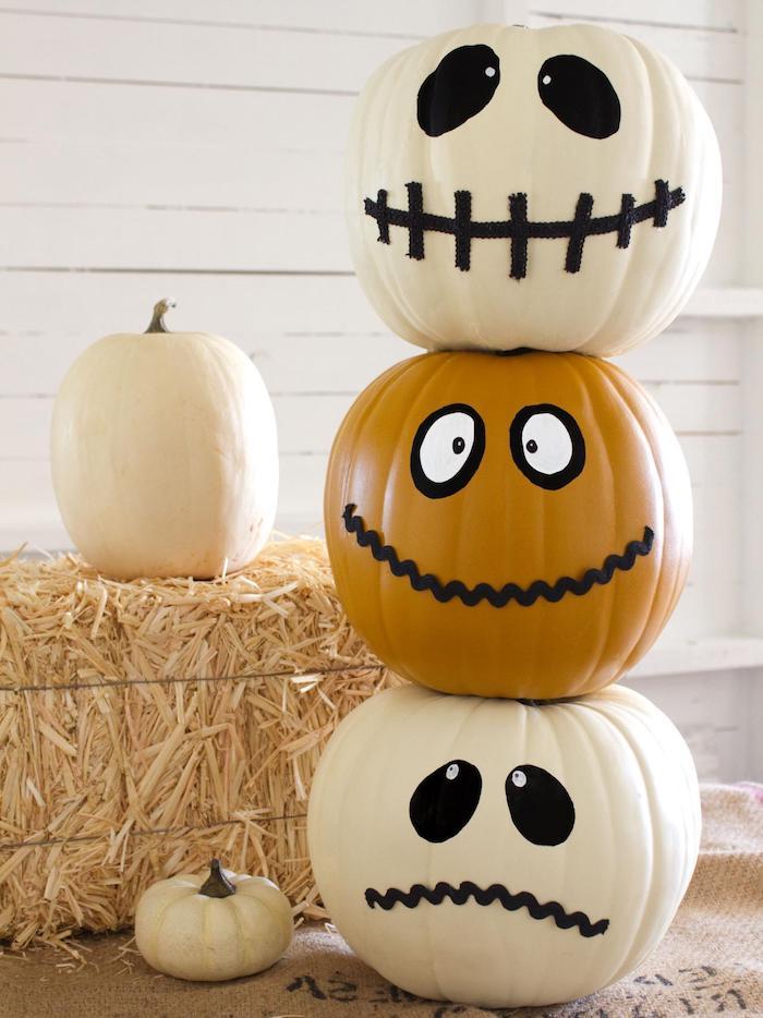 weiße und orange große kürbisse mit schwarzen und weißen großen augen, eine weiße wand aus weißen holzbrettern , traurige und lustige kürbisgesichter malen