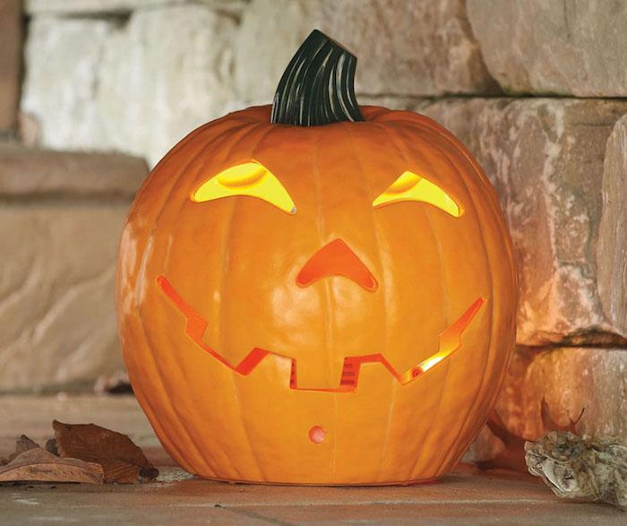 eine wand aus steinen, ein oranger großer kürbis mit gelben augen und einer orangen nase, ein oranger halloween kürbis