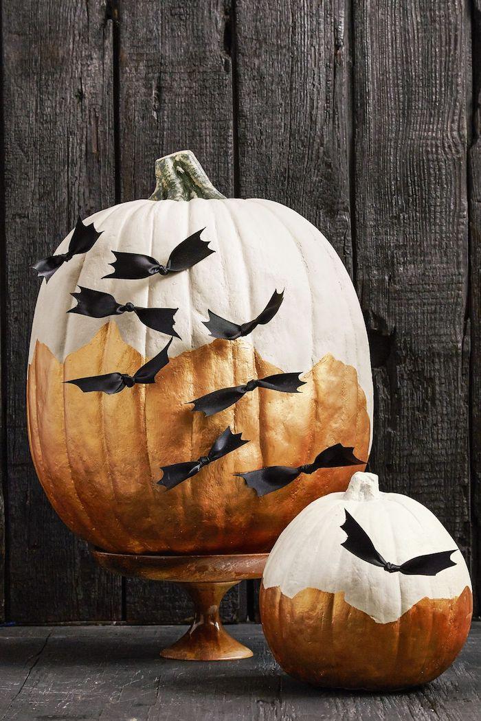 ein großer weißer halloween kürbis mit vielen kleinen schwarzen fliegenden diy fledermäusen aus papier und eine schwarze wand aus schwarzen holzbrettern, fledermaus basteln aus papier
