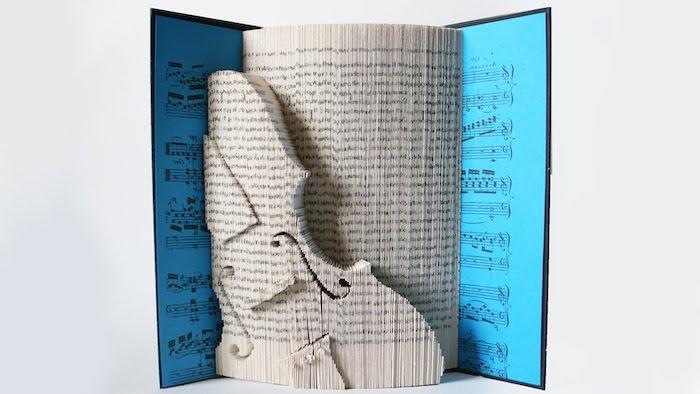 eine groé weiße geige aus papier und vielen weißen gefalteten seiten mit kleinen schwarzen noten, bücher falten idee, ein buch mit einem blauen bucheinband mit kleinen schwarzen noten