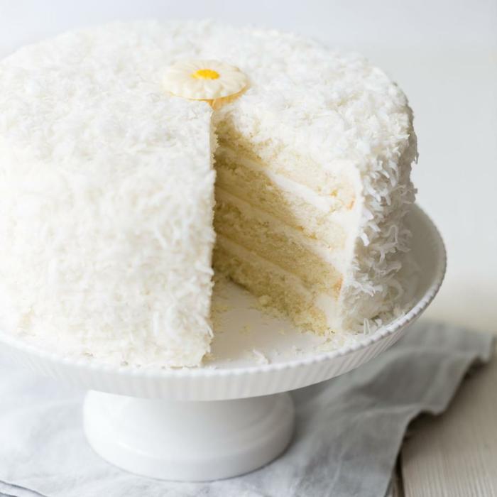 Kokosraspeln, weiße Creme, eine kleine Blume aus Zucker, ausgefallene Torte