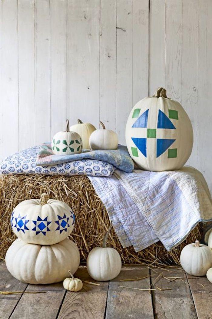 ein boden aus holzbrettern und eine weiße wand aus weißen holzbrettern, viele kleine und große weiße kürbisse mit grünen und blauen figuren, weiße kürbisse malen