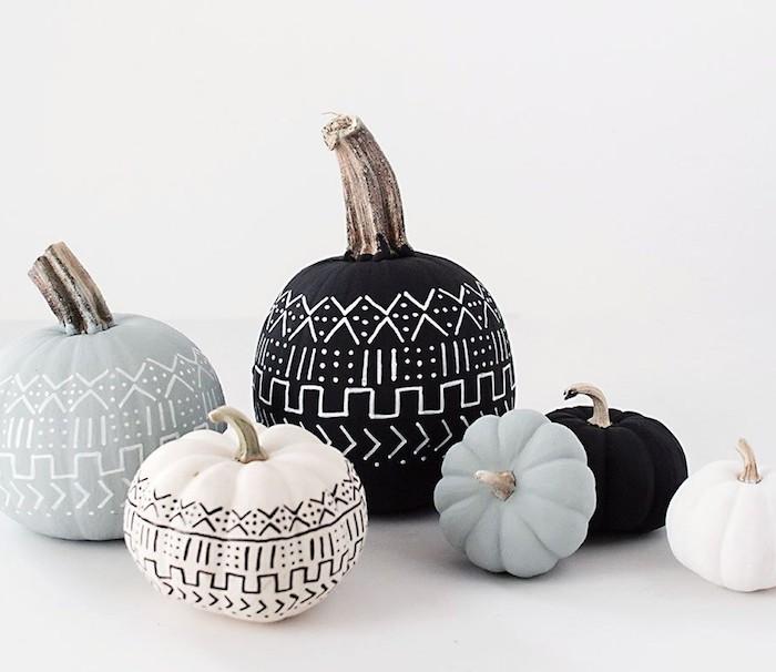 große und kleine bemalte halloween deko kürbisse, graue, weiße und schwarze kürbisse malen