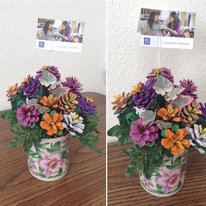 ein brauner tisch aus holz, tannenzapfen bemalen, eine vase mit grünen blättern und mit vielen violetten, weißen und orangen blumen aus bemalten tannenzapfen, tannenzapfen bsateln ideen
