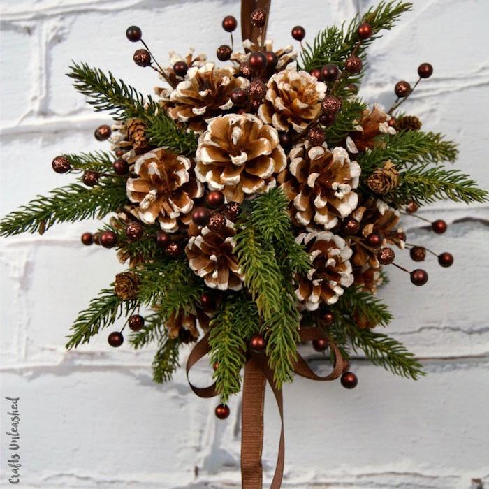 eine weiße wand und eine tannenzapfen deko, basteln mit tannenzapfen weihnachten, ein kranz mit kleinen braunen tannenzapfen und mit grünen ästen und einer langen braunen schleife