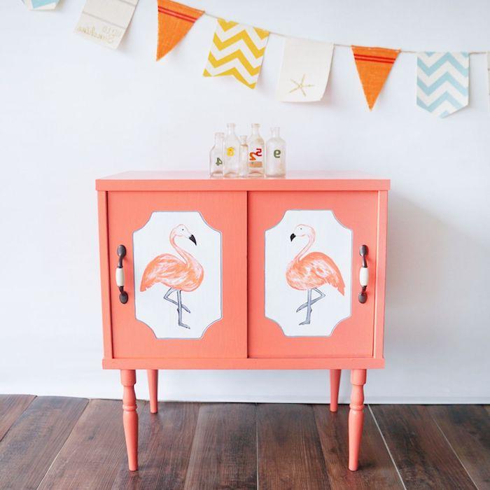 eine n weiße wand und ein boden aus holz und ein schrank mit zwei kleinen pinken flamingos und kleinen flaschen aus glas, flamingo dekoideen