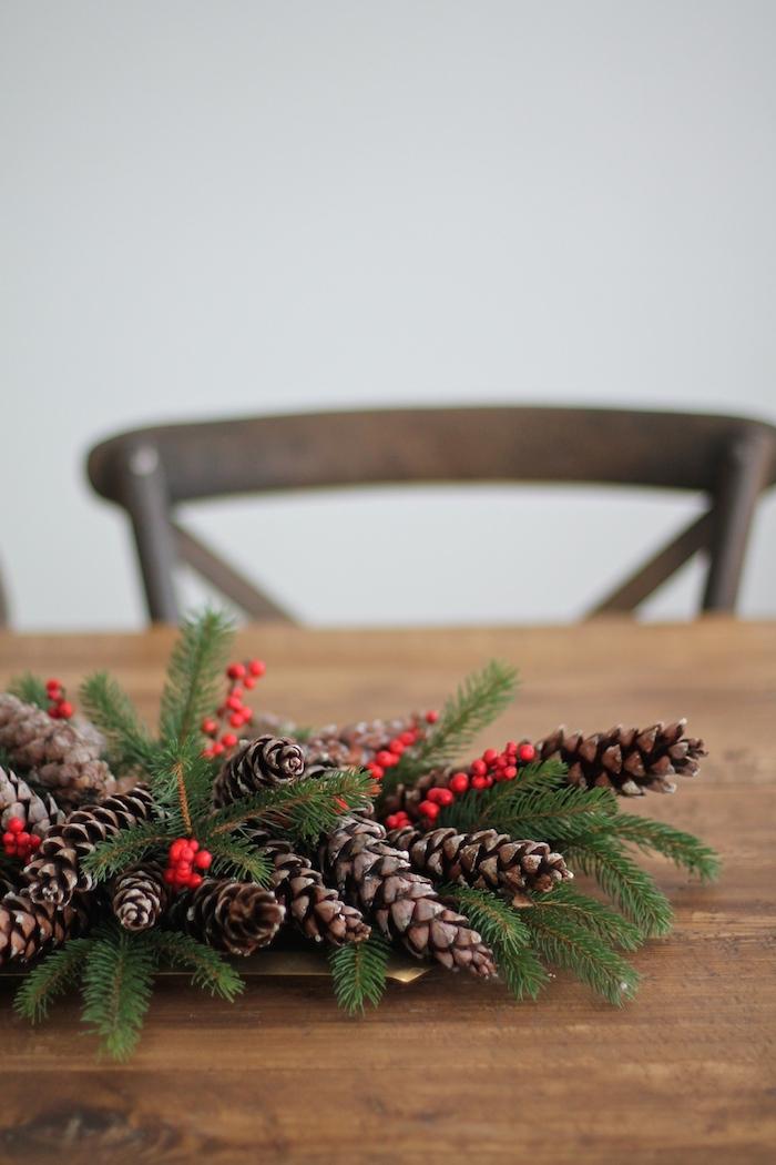 eine weiße wand und ein brauner stuhl und ein tisch aus holz mit einem adventskranz mit vidlen langen braunen tannenzapfen und mit grünen ästen und ilex, einen advenstkranz basteln, basteln mit v weihnachten
