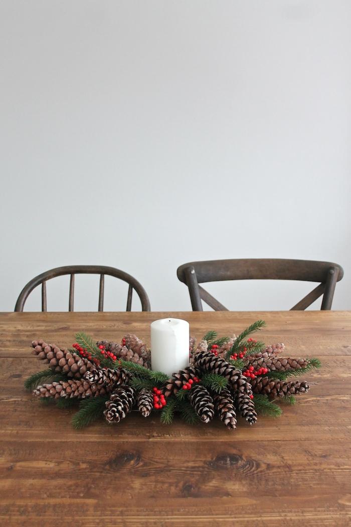 eine weiße wand und ein brauner stuhl und ein tisch aus holz, basteln mit tannenzapfen weihnachten, ein kranz mit einer weißen kerze und mit braunen tannenzapfen und grünen ästen und ilex
