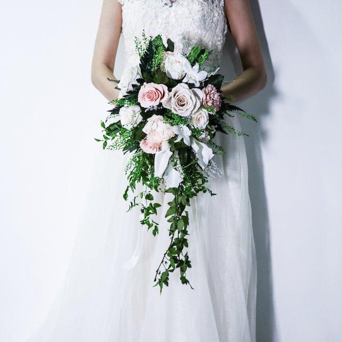 eine weiße wand und eine braut mit einem weißen brautkleid und einem großen wasserfall brautstrauß weiß mit pinken und weißen rosen und vielen grünen blättern, einen weißen brautstrauß gestalten