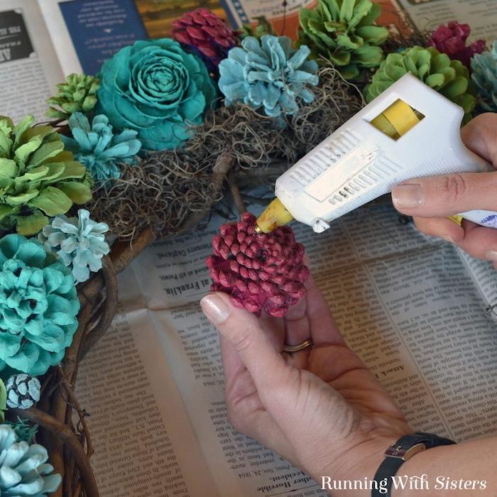 tannenzapfen bemalen anleitung, ein kranz aus gefalteten ästen und mit vielen blauen rosen und bioletten und grünen blumen aus bemalten kleinen tannenzapfen