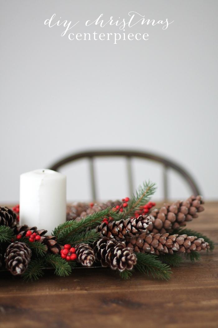 ein brauner tisch aus holz und ein kranz mit einer weißen kerze und mit vielen braunen langen tannenzapfen und grünen ästen und ilex ästen, basteln mit tannenzapfen weihnachten