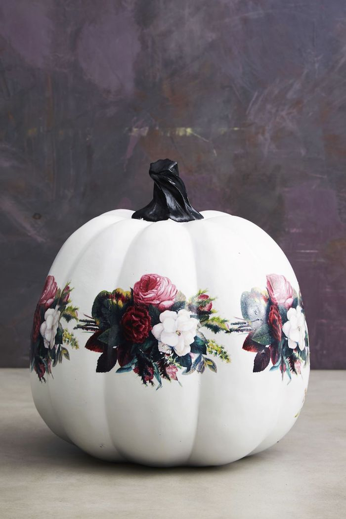 ein weißer großer kürbis mit weißen, roten und violetten rosen mit grünen blättern und eine violette wand, halloween dekoration selber basteln