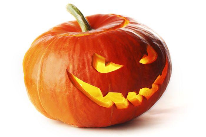 ein oranger großer kürbis mit einem gruseligen kürbisgesicht mit großen gelben augen und schargen orangen zähnen, einen kürbis schnitzen