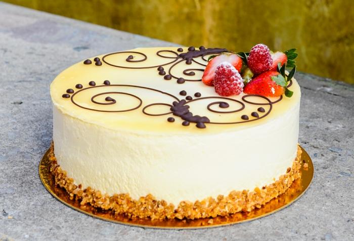gelbe Creme von einer süßen Torte, Himbeeren und Erdbeeren als Dekoration, einfache Tortenrezepte