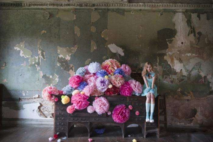 rosa Pompons auf einem Regal, ein Mädchen wie Puppe daneben, Pompon machen