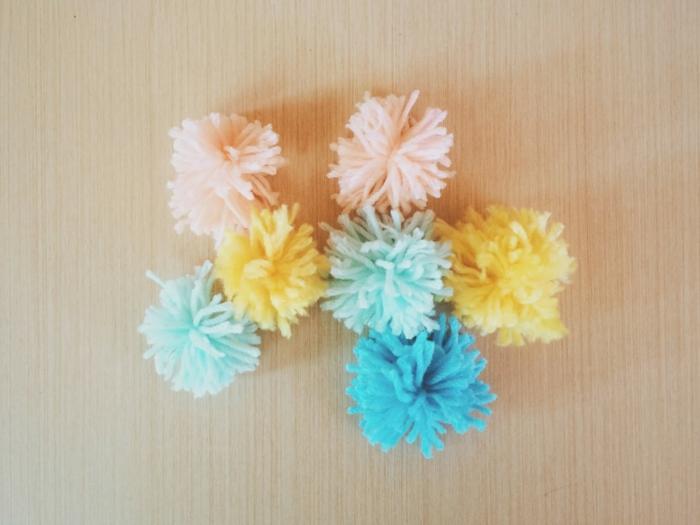 bunte Pompons, Pompon machen, gelbe, blaue und rosa Farbe von Pompons