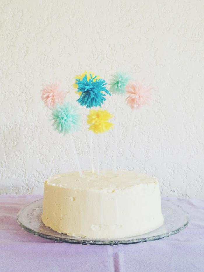 eine weiße Torte mit Pompons Deko, Bommel in blauer, rosa und gelber Farbe