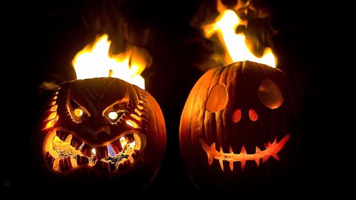 zwei brennende große orange halloween kürbisse, gruselige kürbisgesichter mit großen augen und schwarzen zähnen und mit feuer