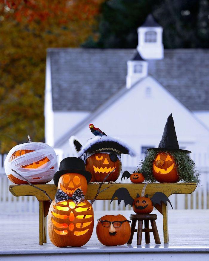 großes weißes haus und viele kleine orange halloween kürbisse mit gelben auhen und nasen, eine hexe mit einem schwarzen hut, eine fledermaus aus einem kleinen kürbis und mit schwarzen flügeln, eine fledermaus selber basteln