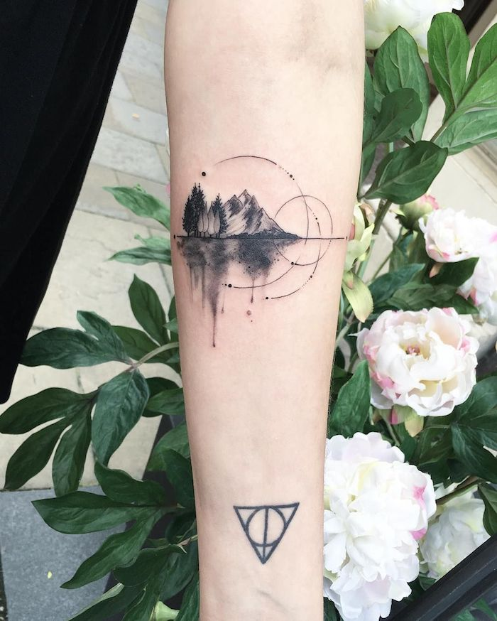 weiße blume mit grünen blättern und eine hand mit einem schwarzen handgelenk tattoo, ein tattoo mit einem schwarzen wald mit schwarzen bäumen und see und bergen