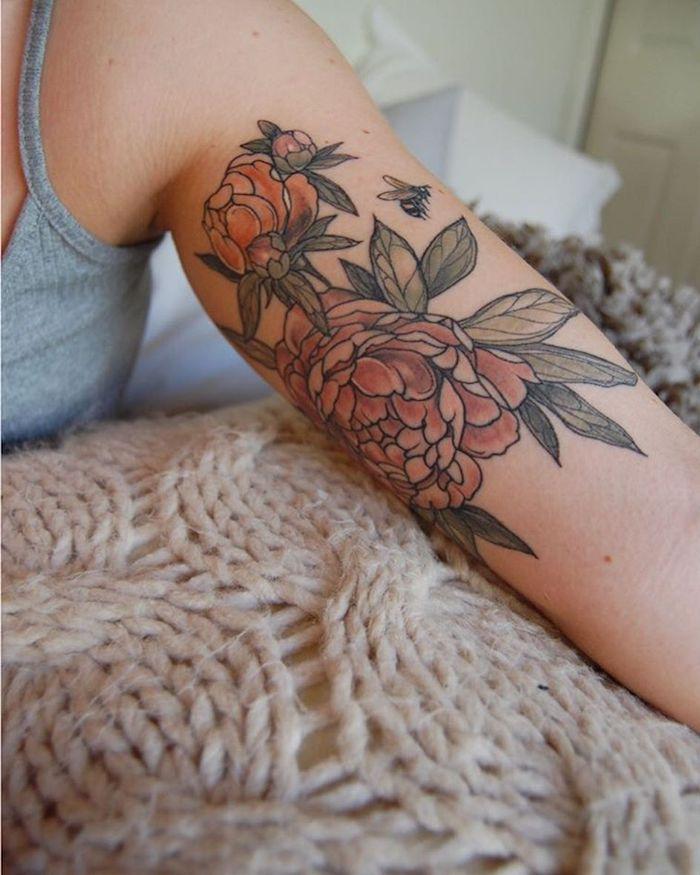 eine hand mit einem großen tattoo mit vielen roten rosen mit vielen grünen bläettern, rosen tattoos ideen für frauen