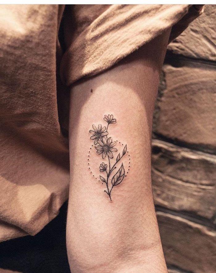 tattoos ideen für frauen, eine junge frau mit einer hand mit einem schwarzen tattoo mit kleinen weißen und schwarzen blumen und blättern und einer sonne