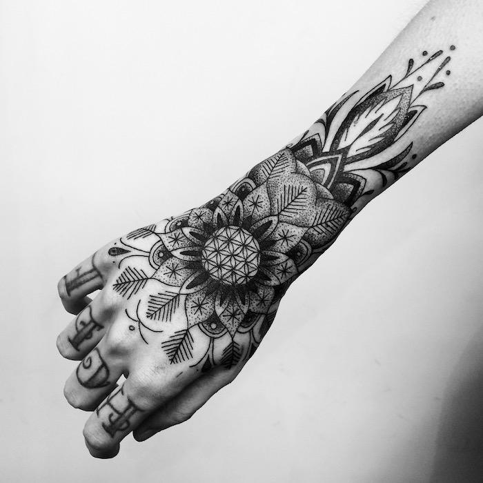 henna tattoos für frauen, eine weiße wand und eine hand mit einem großen schwarzen tattoo mit blumen und blättern