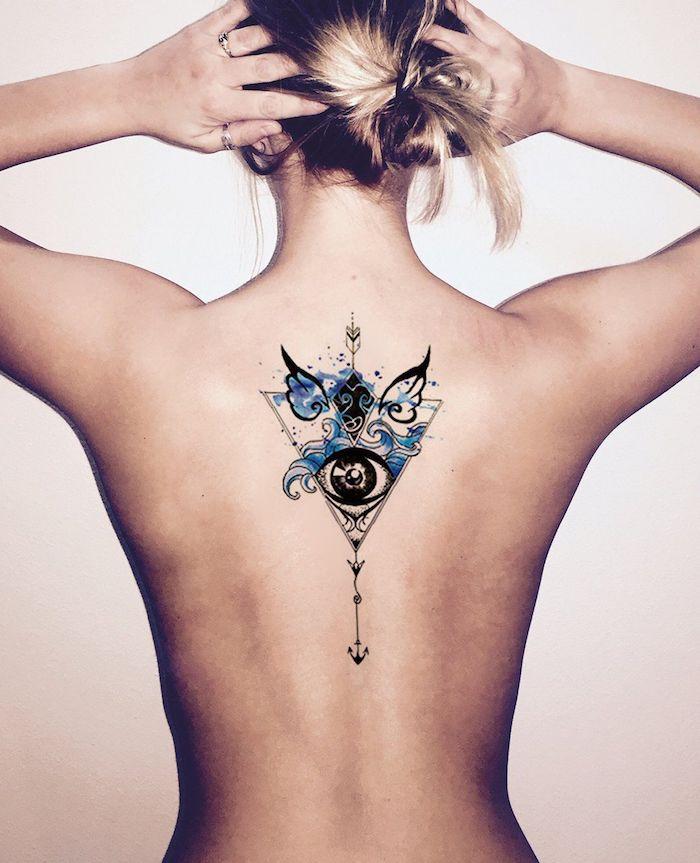 eine junge frau mit einem rücken tattoo mit einer schwarzen auge und mit zwei kleinen schwarzen flügeln und mit blauen wellen
