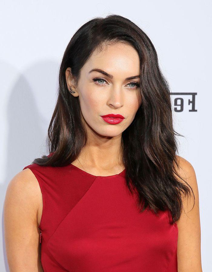 Megan Fox Haarfrisur, lange schwarze Haare, roter Lippenstift und schwarzer Lidstrich, blaue Augen und kühler Hautton, rotes Abendkleid