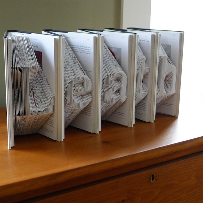 ein schreibtisch aus holz und kleine weiße gefaltete bücher mit weißen gefalteten seiten mit buchstaben