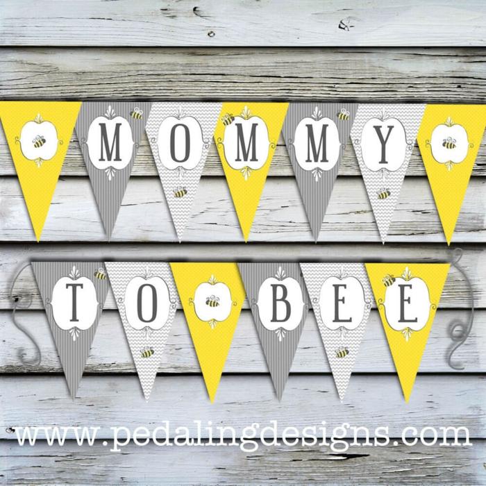 Eine Girlande in gelber, grauer und weißer Farbe an Bretten mit Bildchen von Bienen, Babyparty Ideen