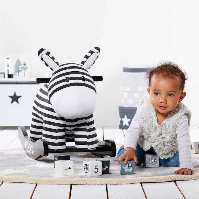 Spielzeug zur Taufe schenken, Schaukelzebra und Würfel, süßes Baby spielt auf dem Boden