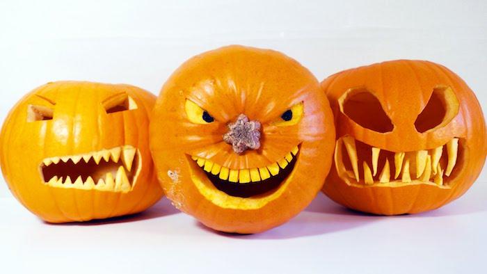 drei orange halloween kürbisse mit gruseligen kürbisgesichtern mit scharfen gelben zähnen und augen, gruselige kürbsgesichter vorlagen