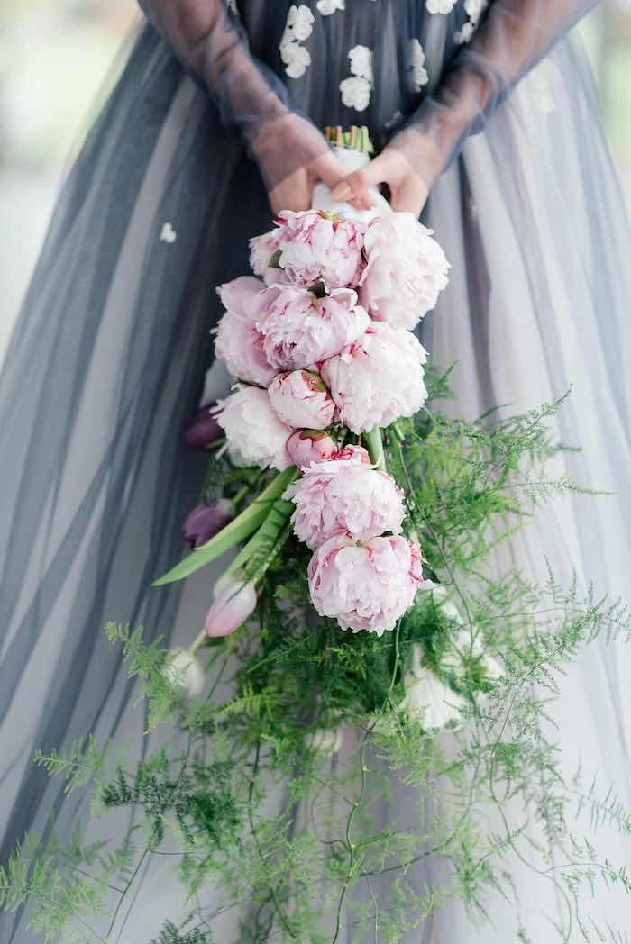 zwei hände mit einem großen brautstrauß mit pinken blumen und violetten und weißen tulpen und grünen blättern, eine braut mit einem violetten kleid