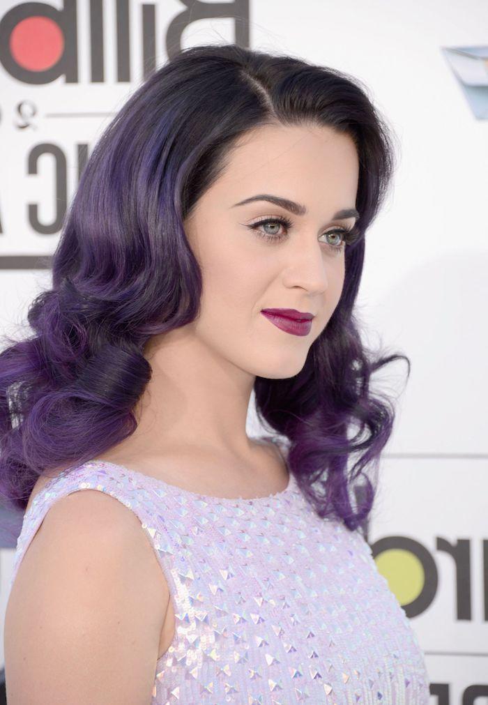 Katy Perry mit Aubergine Haarfarbe, lange Haare, kühler Hautton, schwarzer Lidstrich und lila Lippenstift
