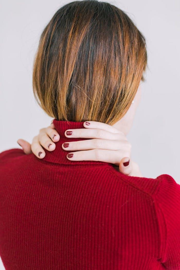 Dunkelbraune Haare mit silbernen Strähnen, roter Nagellack, roter Pullover