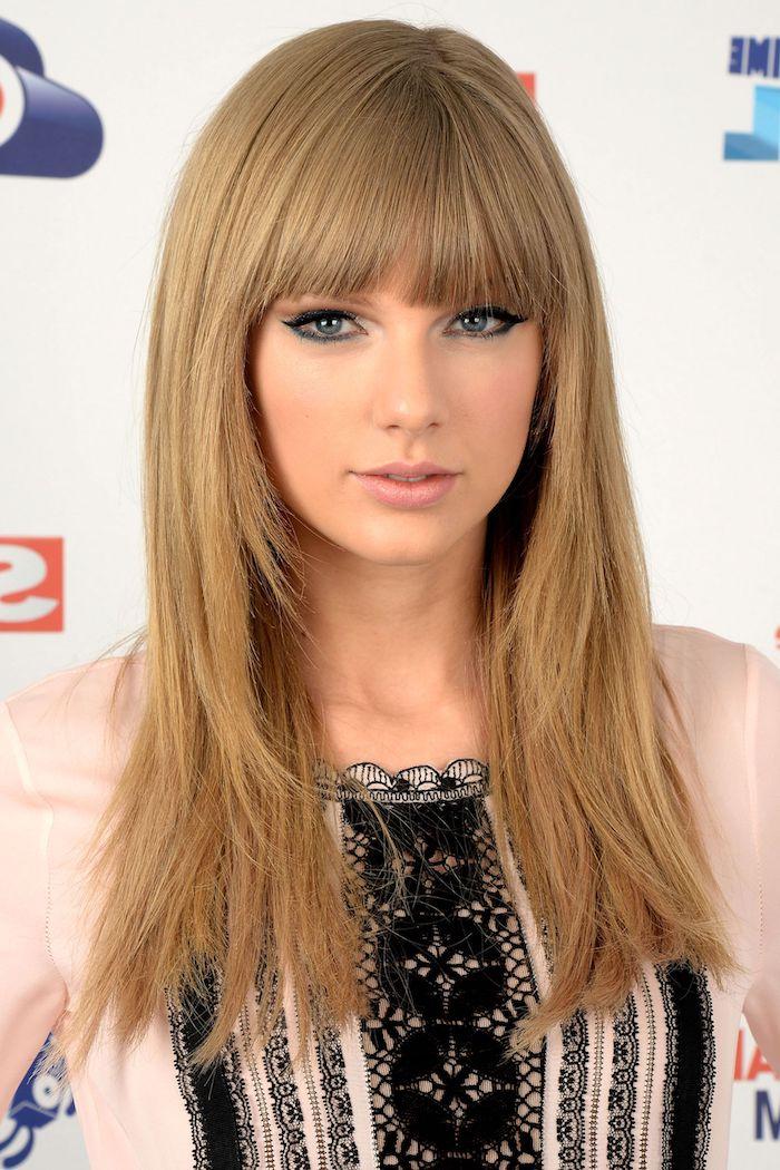 Taylor Swift Haarfrisur, lange dunkelblonde Haare mit geradem Pony, Kleid mit Spitzenmotiven
