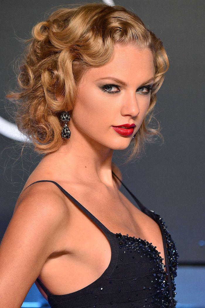 Taylor Swift Frisur, goldbraune Haare, schwarzes Abendkleid mit Pailletten, Smokey Eyes und roter Lippenstift