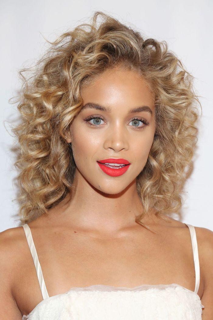 Blonde Locken, mittellange Haare, blaue Augen, roter Lippenstift und schwarze Mascara, weißes Sommerkleid