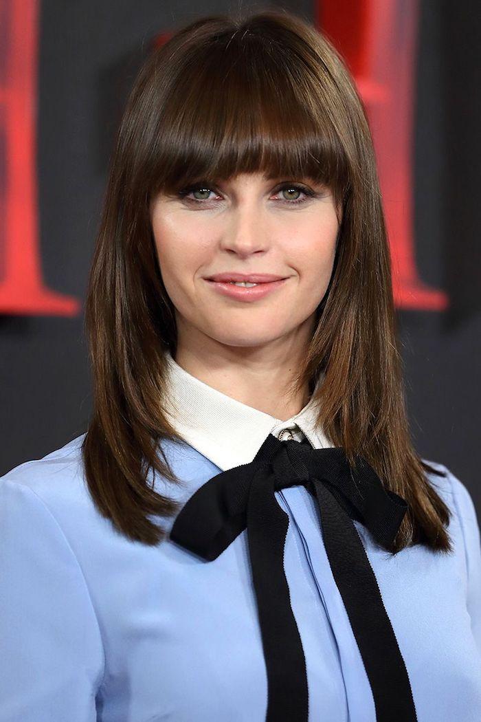 Mittellange braune Haare mit Pony, leichtes Augen Make-up und Lipgloss, hellblaues Hemd mit schwarzer Band