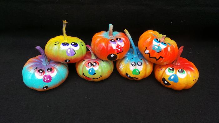 bemalte kleine bunte halloween kürbisse mit coolen kürbisgesichtern mit großen blauen und grünen augen und blauen und roten nasen, ein kürbisgesicht malen