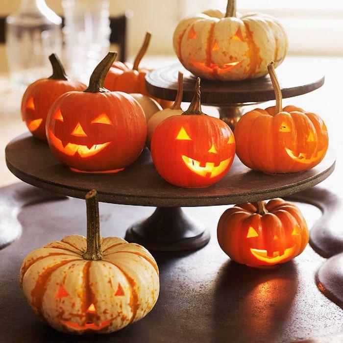 kleine orange halloween kürbisse mit gelben augen und nasen, coole kürbisgesichter schnitzen, halloween deko selber basteln