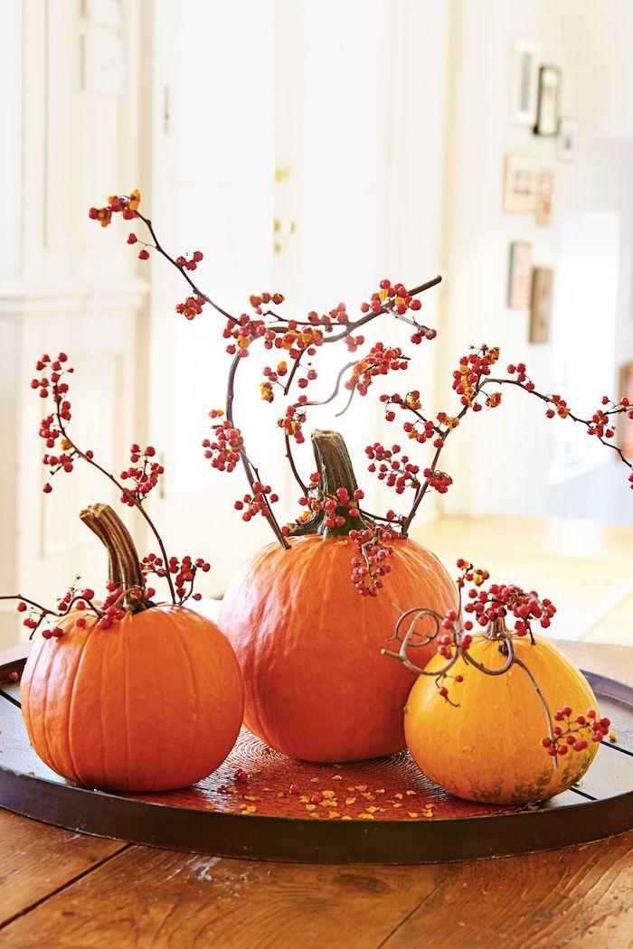 halloween deko mit ästen aus illex mit roten früchten und kleinen und großen orangen und gelben kürbissen, ein tisch aus holz,