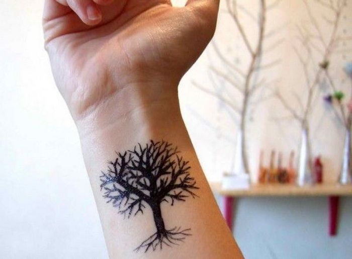 baum tattoo für frauen, eine hand mit einem winzigen tattoo am handgelenk mit einem schwarzen baum mit schwarzen ästen
