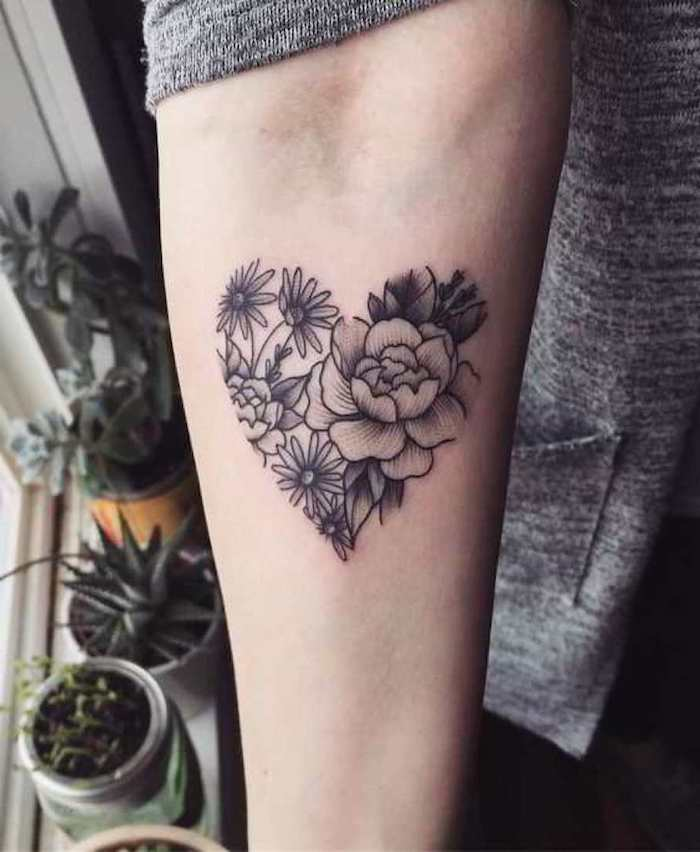 blumentöpfe mit kaktus und grünen pflanzen, eine junge frau mit einer hand mit einem schwarzen tattoo mit einem herzen und blumen