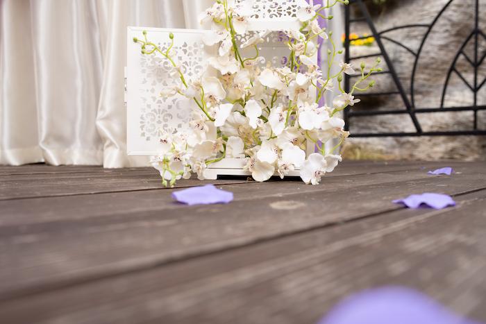 Prachtvolle Dekoration für Hochzeit, weiße Orchideen, lilafarbene Blüten auf dem Boden