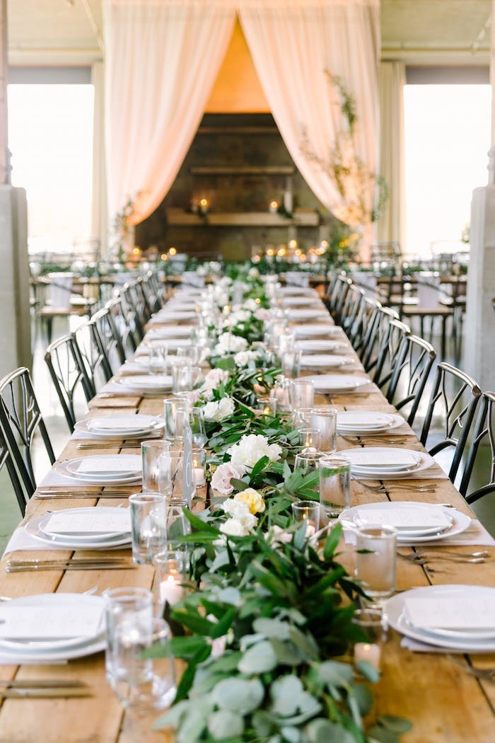 Wunderschöne Tischdekoration für Hochzeit mit vielen Blumen, weiße Teller und Kristallgläser
