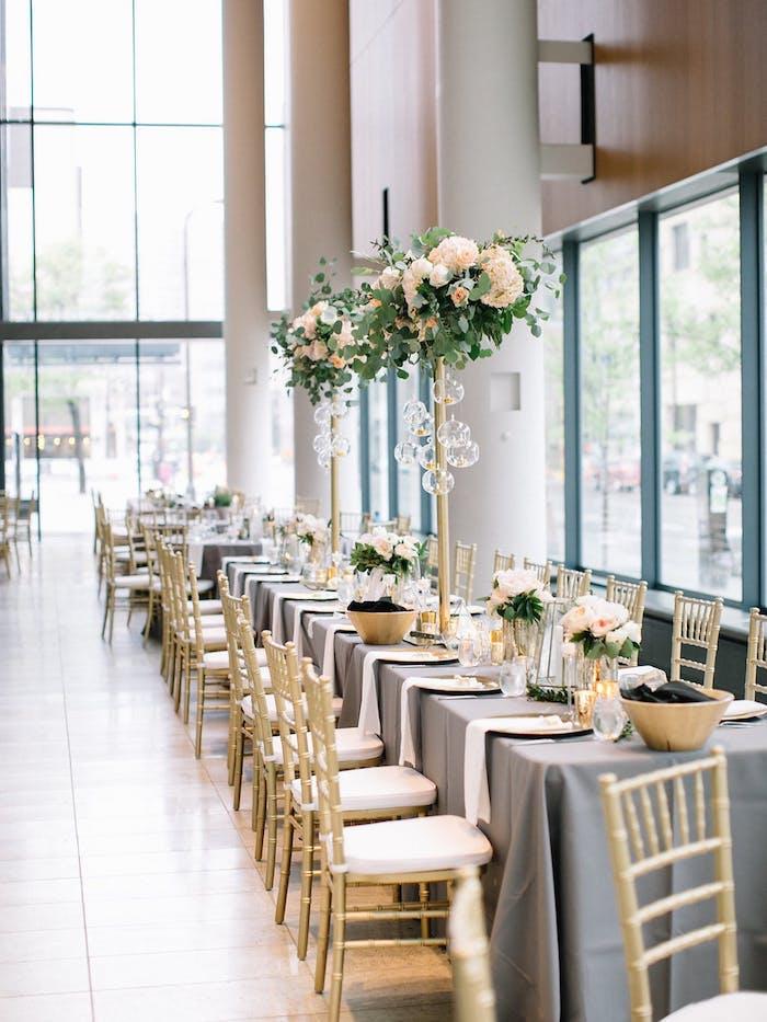 Prachtvolle Tischdekoration für Hochzeit mit vielen Blumen, weiße Rosensträuße in der Luft